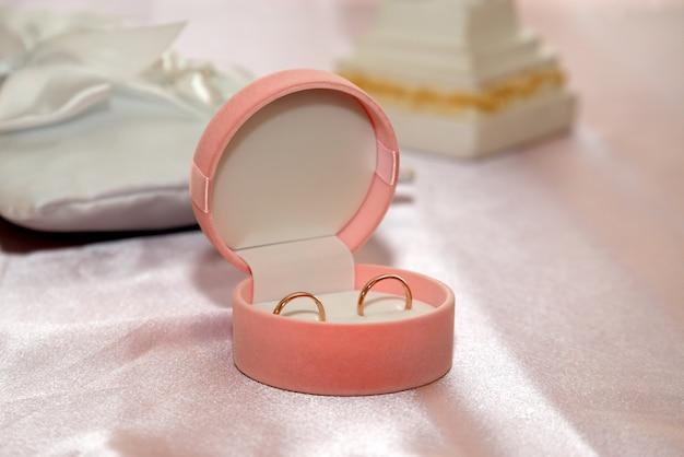 Os anéis de casamento estão na caixa rosa