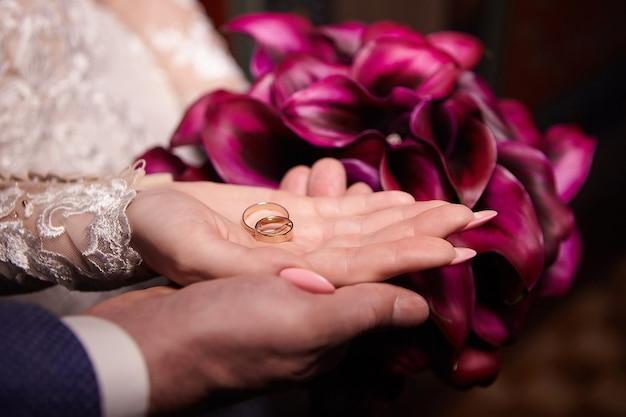 Os anéis de casamento estão nas palmas das mãos masculinas e femininas