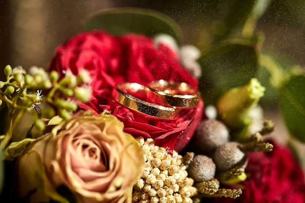 Os anéis de casamento repousam sobre um lindo buquê como acessórios de noiva