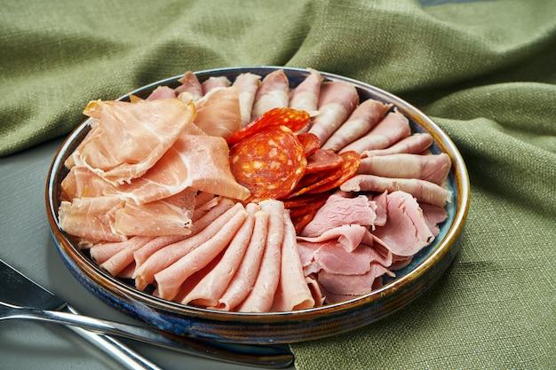 Os antepastos italianos luxuosos da carne ajustaram-se para o vinho na placa cerâmica na tabela de madeira. salame, presunto, presunto e chouriço. feche acima, foco seletivo