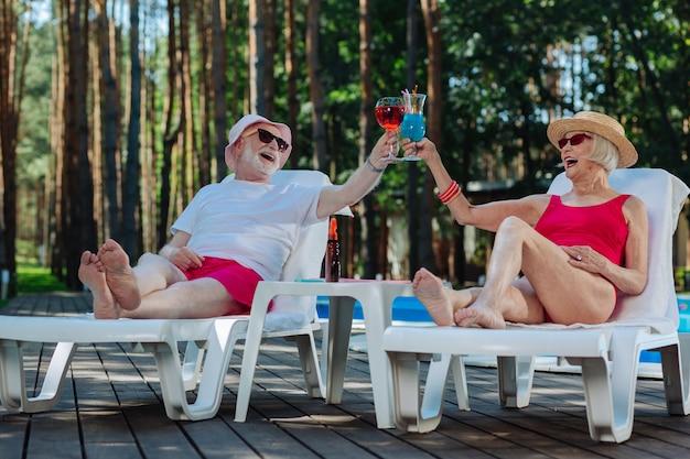 Os aposentados radiantes e felizes sentindo-se memoráveis enquanto passam o fim de semana perto da piscina