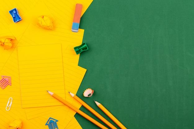 Os artigos de papelaria da escola e a folha de papel alaranjada encontram-se na placa de escola verde que forma um quadro para o texto. perto de lápis e páginas amarrotadas. copie o espaço flat lay vista superior conceito educação