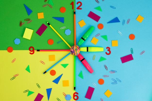 Os artigos de papelaria representam os ponteiros do relógio.