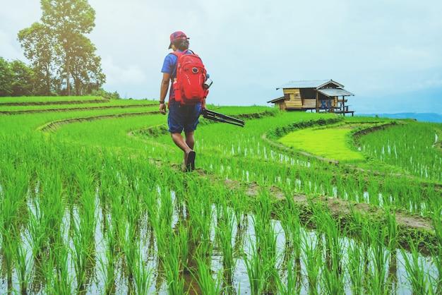 Os asiáticos do homem viajam natureza. viajar relaxar. andar a tirar uma foto no campo. no verão