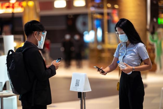 Os asiáticos escaneiam códigos qr para fazer check-in em lojas de departamento. eles usam máscaras para se proteger contra vírus.