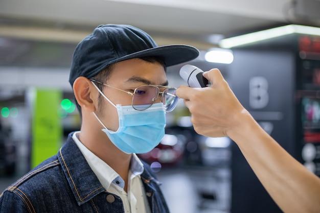 Os asiáticos medem a temperatura da gripe e verificam se há um coronavírus. ele usando máscara de proteção no rosto