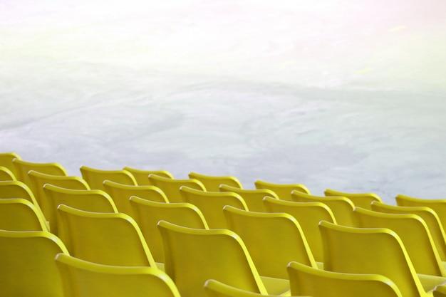 Os assentos amarelos plásticos vazios enfileiram na mostra interna do estádio ou no fundo do lugar do campo de esporte.