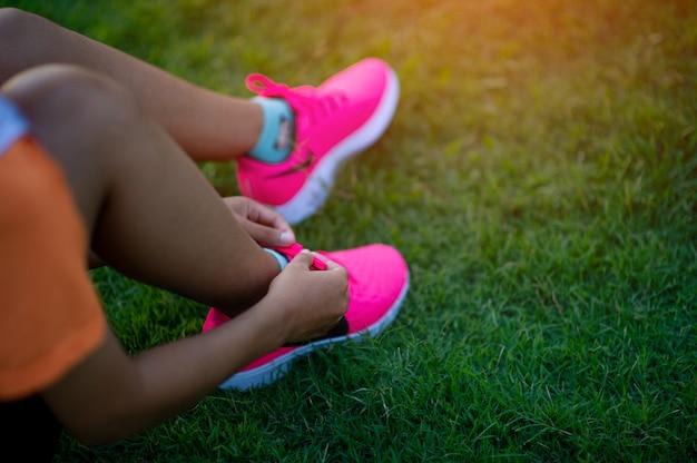 Os atletas amarram os sapatos antes de se exercitarem para uma boa saúde.