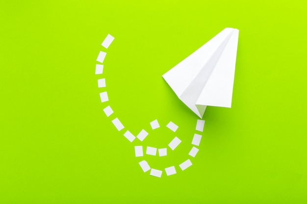 Os aviões de papel conectaram com as linhas pontilhadas no fundo verde. conceito de negócios