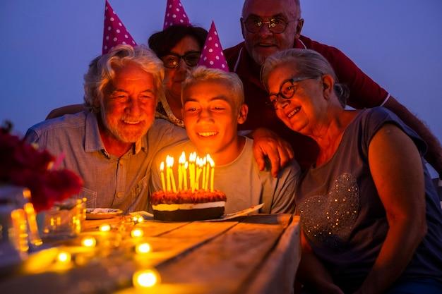 Os avós idosos e o jovem adolescente celebram o aniversário juntos à noite em casa com bolo e velas se divertindo e curtindo o amor e a amizade na festa com diferentes gerações