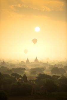 Os balões de ar quente da cena do nascer do sol voam sobre o campo antigo da cidade do pagode em bagan myanmar.
