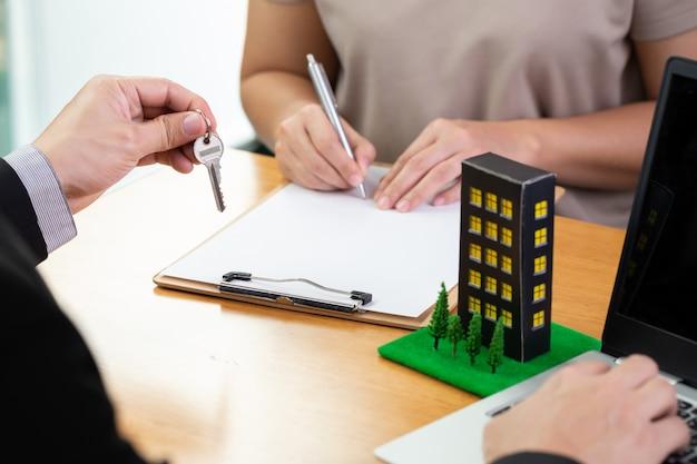 Os bancos aprovam empréstimos para comprar condomínio e o cliente está assinando o contrato. casa de hipoteca e conceito imobiliário