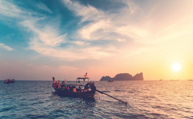 Os barcos de pesca com os turistas no oceano.