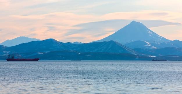 Os barcos de pesca na baía com o vulcão em kamchatka