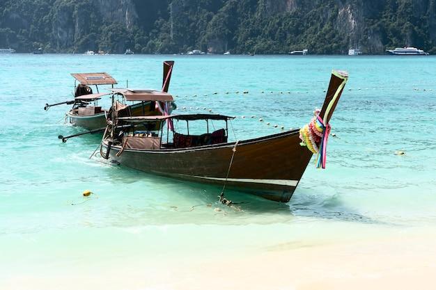 Os barcos longos estão na ilha de phi phi. água azul clara pode ser vista.