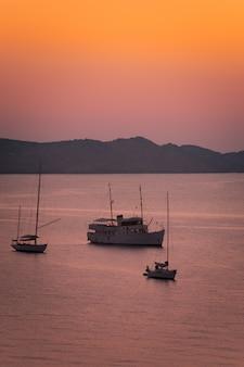 Os barcos que veem o por do sol em agosto na praia de cavalleria na costa norte de menorca, espanha.