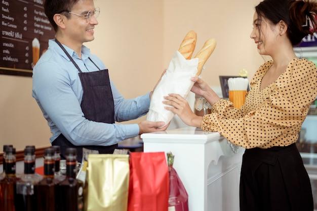 Os baristas entregam uma xícara de café quente e uma padaria para oferecer ao cliente na cafeteria