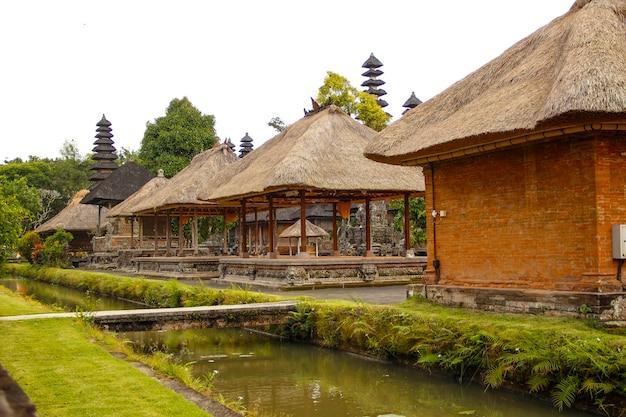 Os belos edifícios do templo da família real em bali separados por um rio de água. indonésia