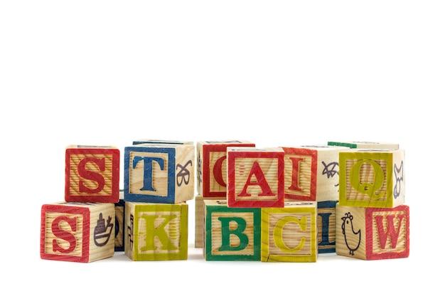 Os blocos de alfabeto de madeira em um fundo branco