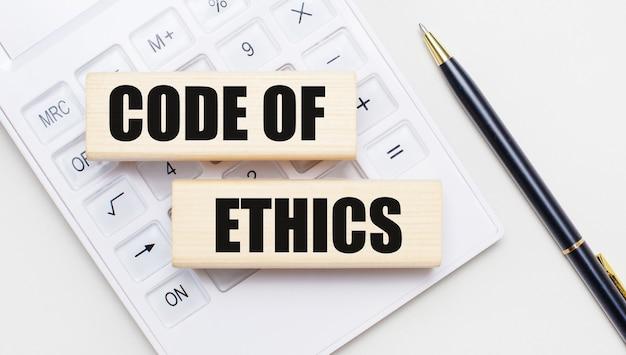 Os blocos de madeira com o texto código de ética estão sobre um fundo claro em uma calculadora branca. perto está uma alça preta. conceito de negócios