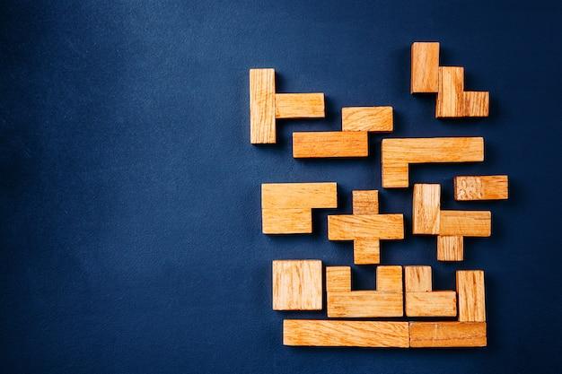 Os blocos de madeira das formas geométricas diferentes arranjam na figura contínua em um fundo escuro.