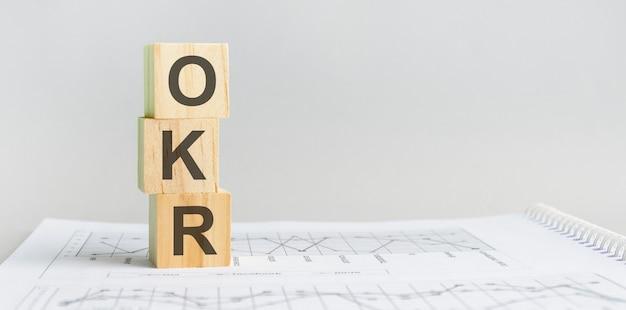 Os blocos de madeira okr estão no fundo cinza de papel. conceito de negócios. espaço para texto à direita. vista frontal. okr - abreviação de objetivos e resultados-chave