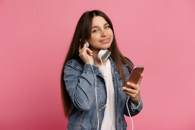 Os blogueiros jovens alegres usam suas listas de reprodução favoritas isoladas em rosa