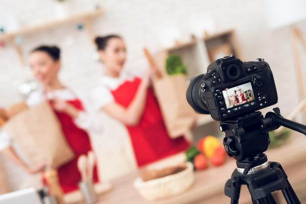 Os blogueiros seguram pacotes com comida para a câmera.