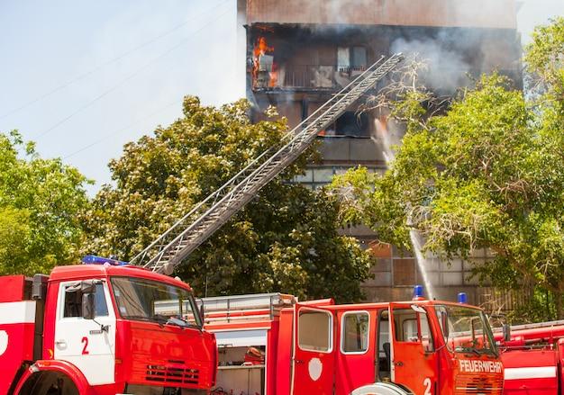 Os bombeiros extinguem um incêndio em um edifício residencial alto.