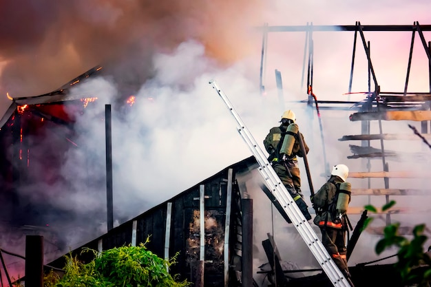 Os bombeiros lutam contra um incêndio contra um fundo de fumaça branca espessa ... os bombeiros nas escadas extinguem o telhado de uma casa particular ou celeiro.