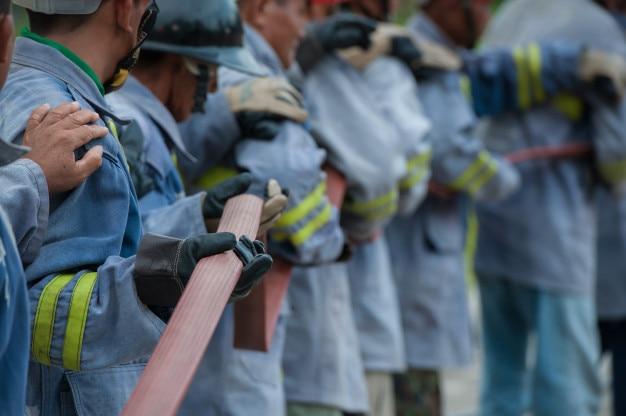 Os bombeiros segurando a mangueira de incêndio