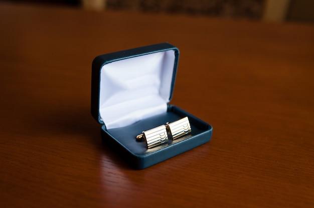 Os botões de punho masculinos elegantes são de forma retangular.