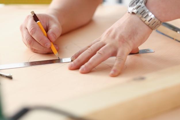 Os braços do trabalhador que fazem a estrutura planeiam no close up de papel escalado. trabalho manual diy inspiração melhoria correção de emprego loja gráfica marcenaria startup local de trabalho idéia designer carreira educação industrial