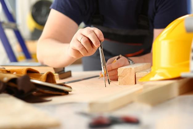 Os braços do trabalhador que fazem a estrutura planeiam no close up de papel escalado. trabalho manual diy inspiração melhoria correção de emprego loja gráfica marcenaria startup local de trabalho idéia designer carreira régua de barra de madeira