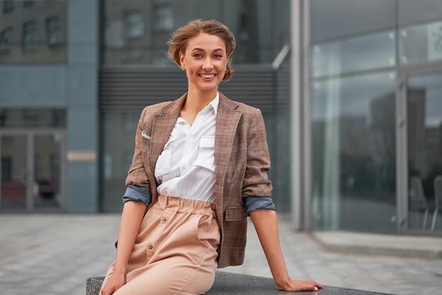 Os braços eretos do empresário bem sucedido da mulher de negócios da mulher de negócios cruzaram o exterior do edifício corporativo ao ar livre. sorriso feliz, caucasiano, confiança, profissional, mulher de negócios, meia-idade