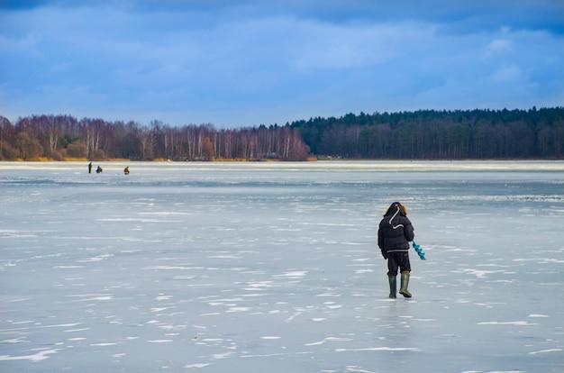 Os bravos homens no gelo para a pesca de inverno
