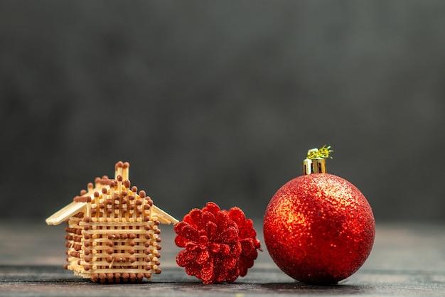 Os brinquedos da árvore de natal combinam com a casa no escuro espaço livre