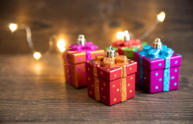 Os brinquedos de ano novo em forma de caixas de presente estão sobre uma mesa de madeira velha. ano novo e o conceito de natal.