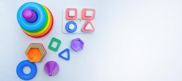 Os brinquedos educativos para crianças, uma pirâmide e classificadores, encontram-se em um fundo branco com um lugar para o topo do texto ...
