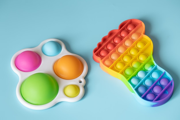 Os brinquedos infantis da moda e anti-stress estouram e abrem um close-up com uma covinha simples em uma superfície azul