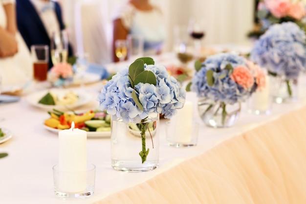 Os buquês de oferta de hortênsias azuis estão em óculos na mesa de jantar