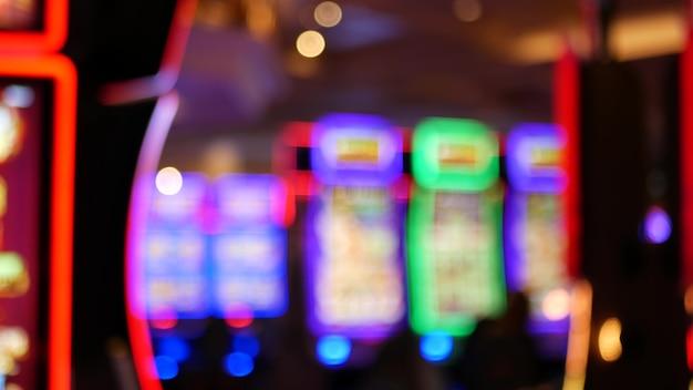 Os caça-níqueis desfocados brilham no cassino, em las vegas, eua. caça-níqueis de néon de jogo borrado