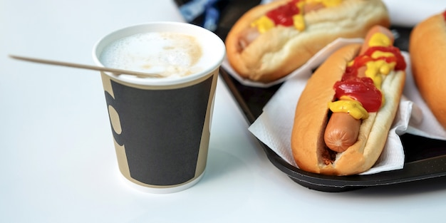 Os cães, molho, ketchup, café com leite em uma xícara. café com leite