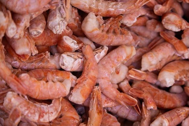 Os camarões crescidos orgânicos refrigeraram no gelo, vista superior. textura abstrata de fundo e comida.