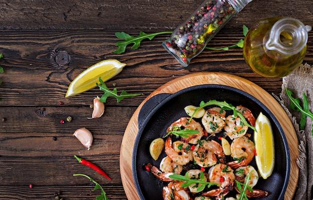 Os camarões dos camarões roasted na manteiga de alho com limão e salsa no fundo de madeira.