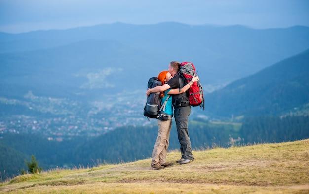 Os caminhantes felizes estão abraçando, estando com as trouxas na estrada na montanha com paisagem bonita da montanha no fundo borrado. espaço da cópia