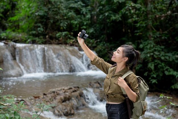 Os caminhantes femininos tiram fotos de si mesmos