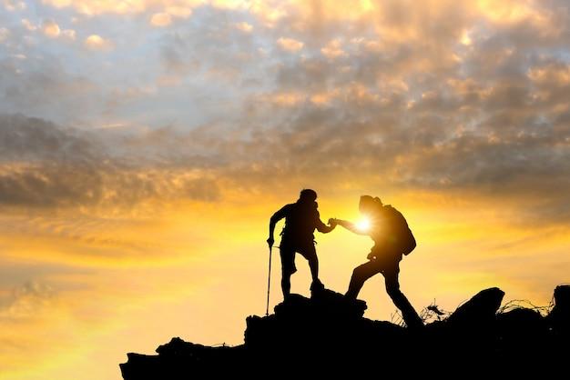 Os caminhantes masculinos e fêmeas que escalam acima o penhasco da montanha e um deles que dão a mão amiga.