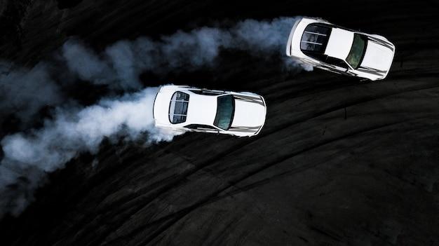 Os carros aéreos da vista superior dois que derivam a batalha no autódromo, dois carros batem a tração, opinião dos carros de corridas de cima de.