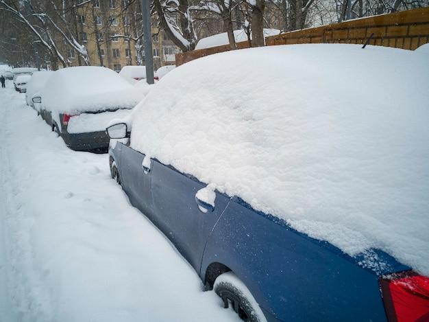 Os carros estacionados na beira da estrada ficam cobertos por uma espessa camada de neve após uma nevasca.